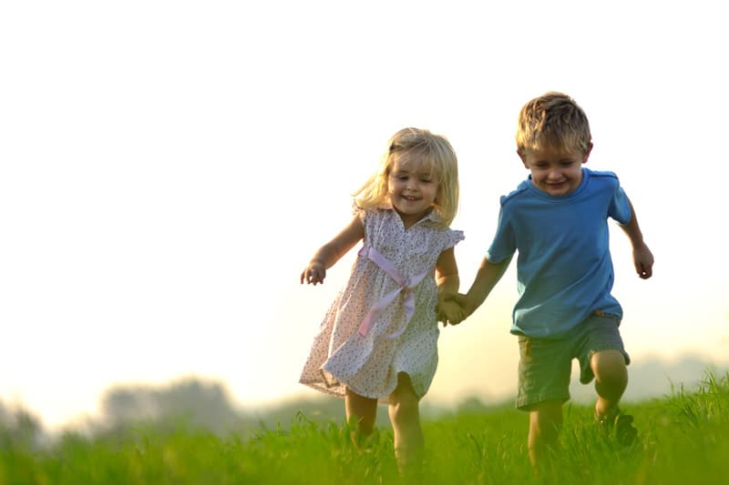 Little boy and girl running on the field