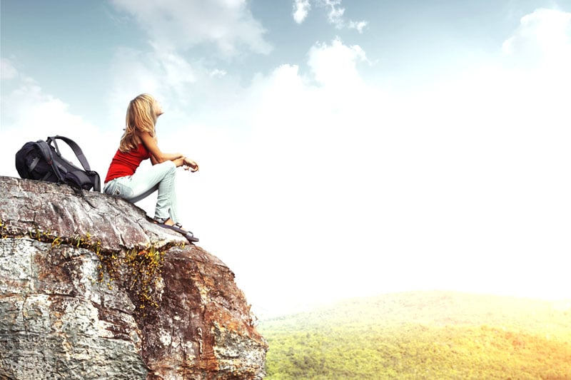Girl sitting on cliff