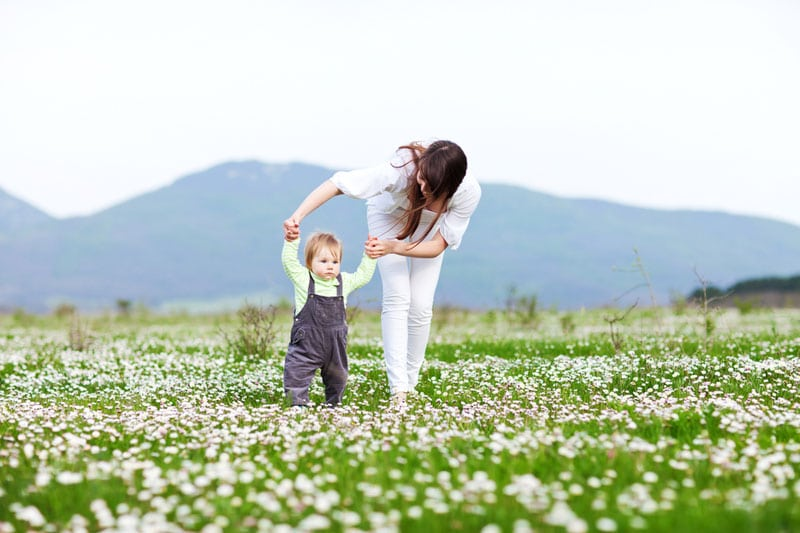 Mother teaching her child to walk on the field
