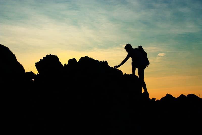 Silhouette of man climbing mountain