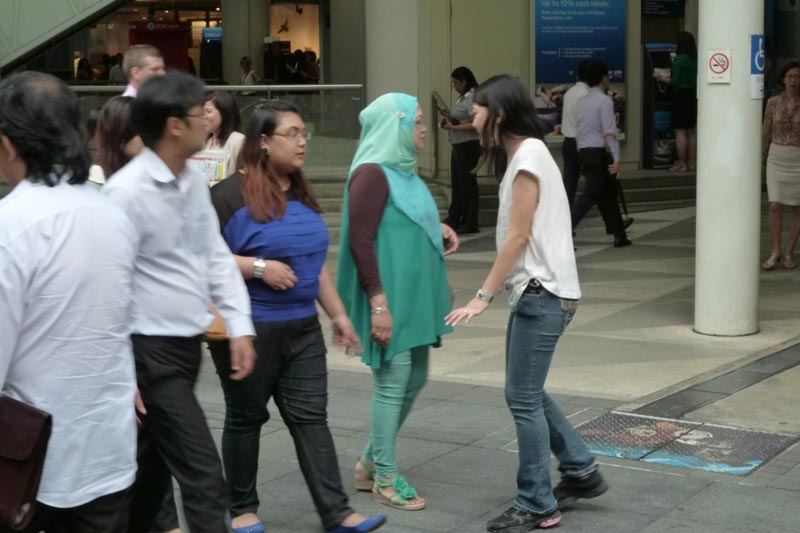 Celes approaching a trio of Malay ladies for a hug