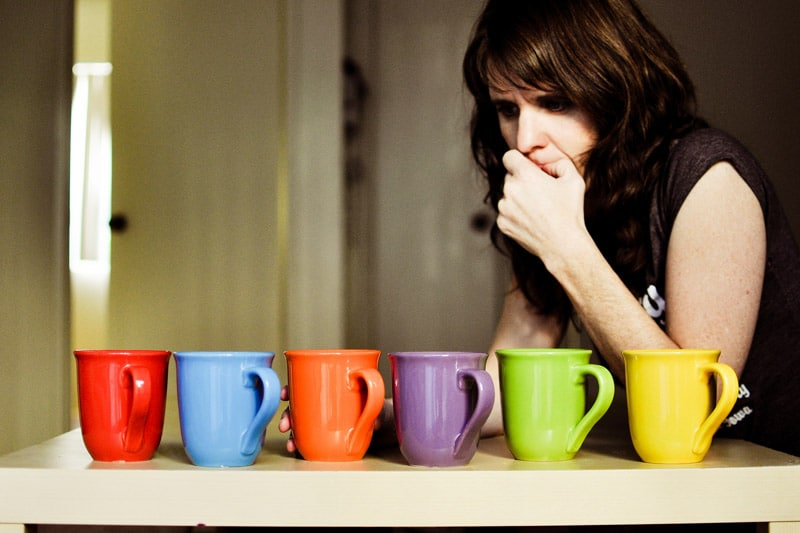 Woman thinking, having to choose between different colored cups