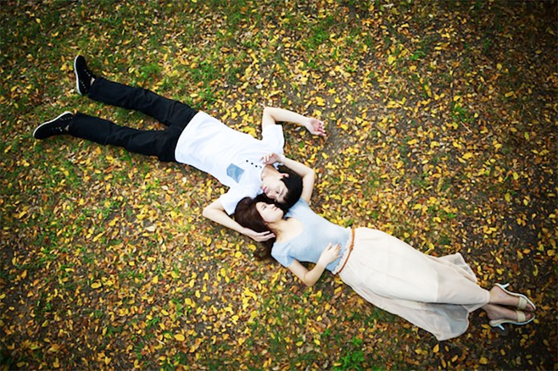 Asian couple lying down in garden