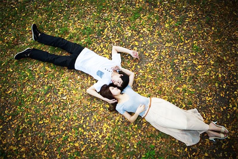 Asian couple lying down in garden