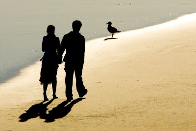 Silhouette of a couple, walking along the beach
