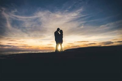 Silhouette of a couple against a sunrise