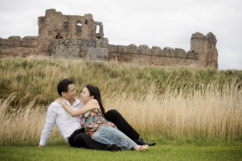 Engagement shoot: Lying at the wheat field outside Tantallon Castle