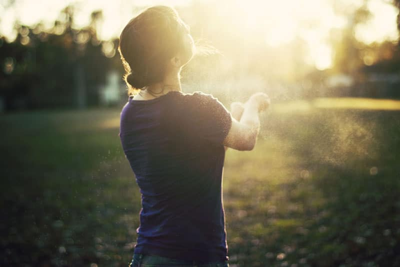 Girl in bright light, standing on field