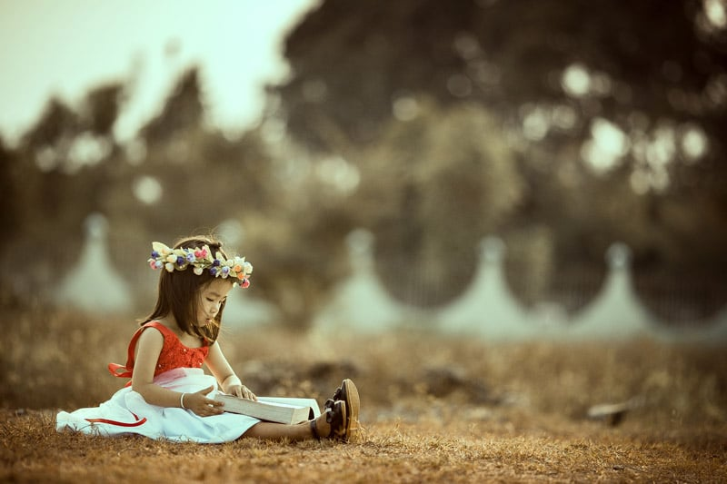 Little girl wearing a flower crown, sitting on a field