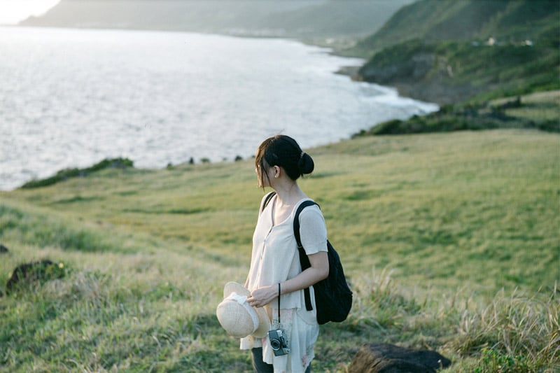 Girl standing on a field, looking at the sea