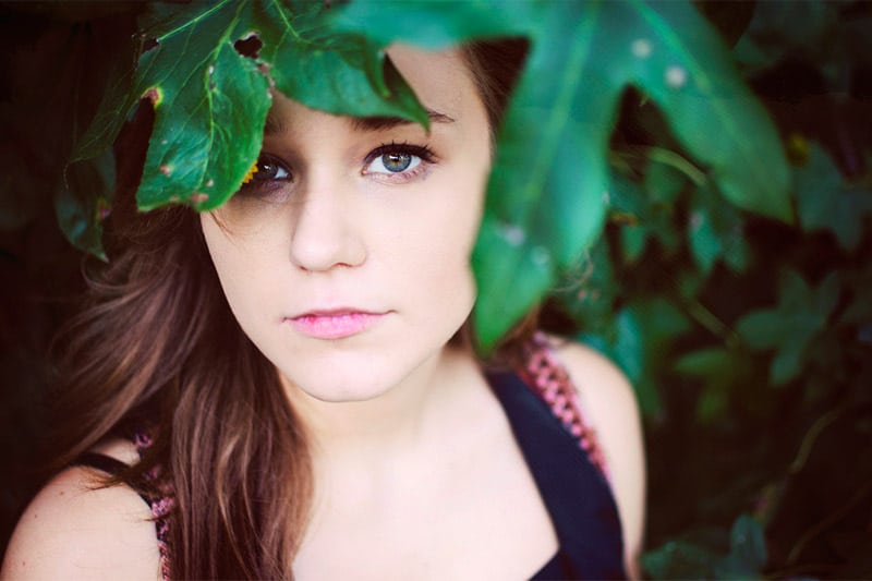 Girl peering from under leaves
