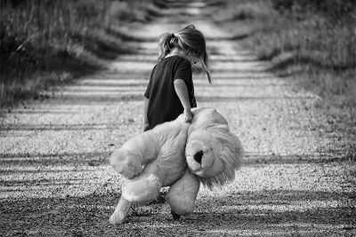 Sad girl, walking away with her teddy bear