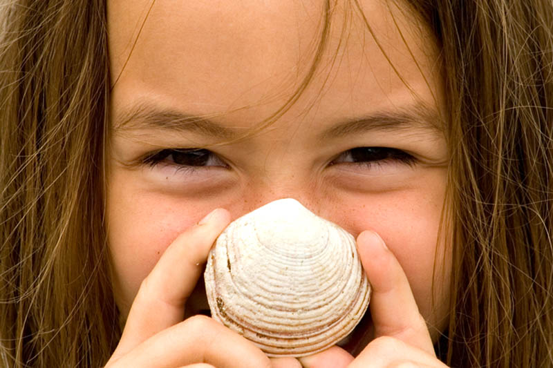 Girl smiling with a seashell