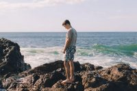 Guy standing on the rocks, by the sea