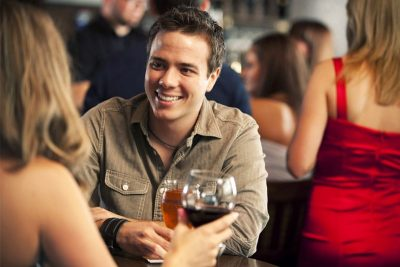 Guy smiling at his date, at a bar; Dating