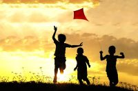 Children flying kite on a field