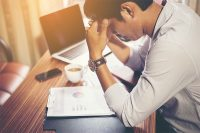 Man feeling stressed at his work desk: Dealing with Digital Burnout