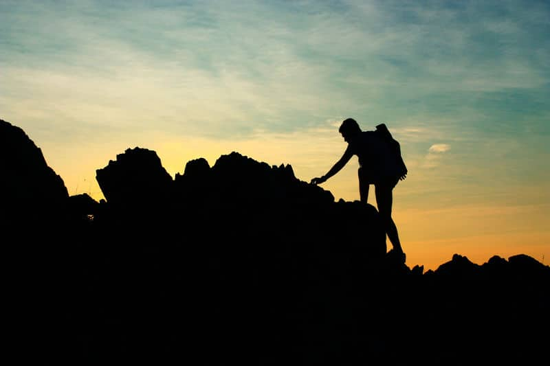 Silhouette of man climbing mountain