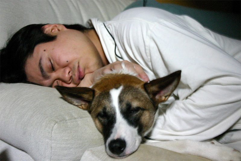 Man sleeping with his dog