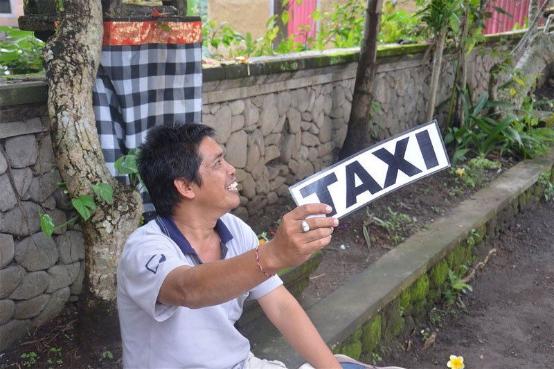 "Ubud: A driver holding a sign saying ""TAXI"""